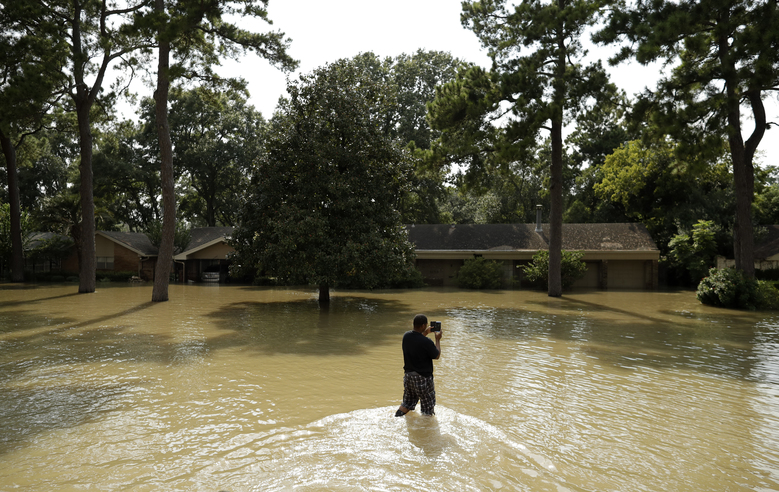 A man takes a photo of a flooded home Friday, Sept. 1, 2017, in Houston. Thousands of people have been displaced by torrential rains and catastrophic flooding since Harvey slammed into Southeast Texas last Friday. (AP Photo/Gregory Bull) CAGB112 CAGB112
