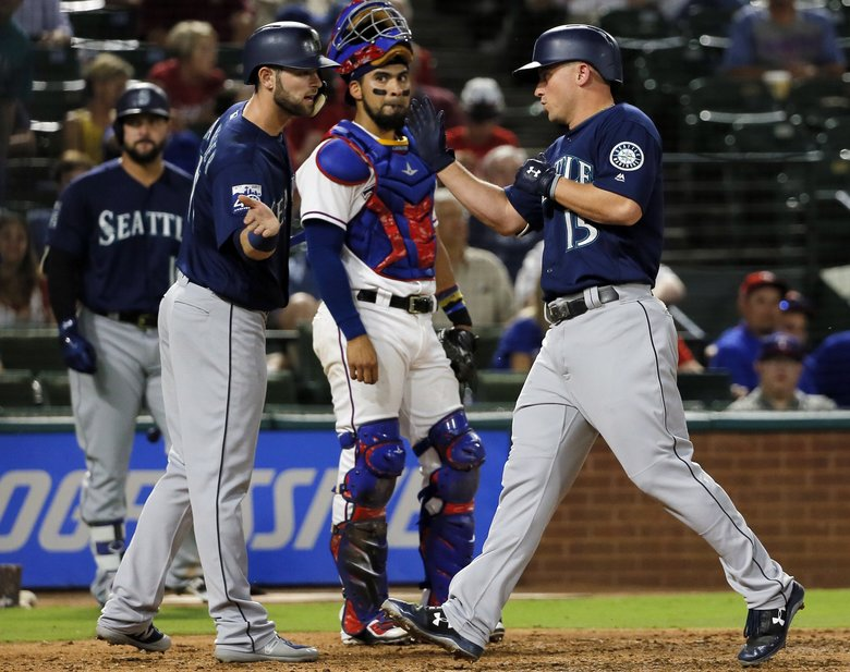 Seattle Mariners' Mitch Haniger congratulates Kyle Seager, right, on his three-run home run as Texas Rangers catcher Robinson Chirinos watches during the third inning of a baseball game, Tuesday, Sept. 12, 2017, in Arlington, Texas.  (Tony Gutierrez/AP)
