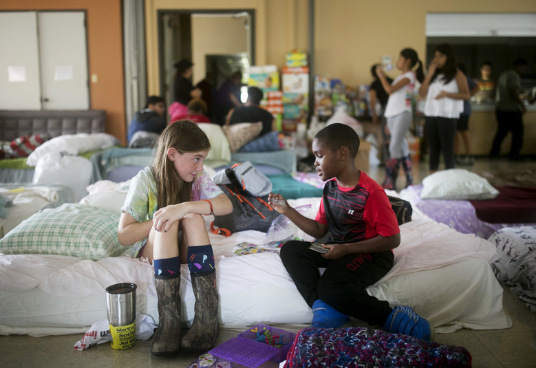 FILE – Volunteer Elizabeth Hill, 8, plays with evacuee Skyler Smith, 7, at a shelter at St. Thomas Presbyterian Church in west Houston as Tropical Storm Harvey continues to affect the area Tuesday, Aug. 29, 2017. The deluge damaged 156,000 dwellings, according to the flood control district for Harris County, which includes Houston. And the storm's death toll of 42 ranks it as the mainland's seventh deadliest hurricane in 50 years. (Jay Janner/Austin American-Statesman via AP)