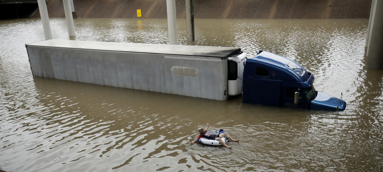 FILE – After helping the driver of the submerged truck get to safety, a man floats on the freeway flooded by Tropical Storm Harvey on Sunday, Aug. 27, 2017, near downtown Houston. Harvey was the first Category 4 storm to make landfall in the United States since 2004. (AP Photo/Charlie Riedel)