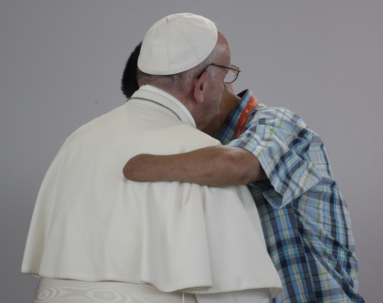 Former FARC rebel Carlos Juan Carlos Murcia, who lost his left hand, embraces Pope Francis during a prayer meeting for reconciliation at Las Malocas Park in Villavicencio, Colombia, Friday, Sept. 8, 2017. Pope Francis is visiting the area once besieged by leftist rebels for an event that brings victims and victimizers together. (AP Photo/Andrew Medichini)