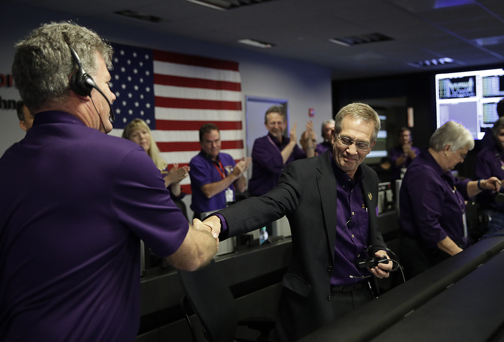 Project manager Earl Maize, center, shakes hands with Bill Heventhal in mission control at NASA's Jet Propulsion Laboratory, Friday, Sept. 15, 2017, in Pasadena, Calif. after confirmation of Cassini's demise. Cassini disintegrated in the skies above Saturn early Friday, following a remarkable journey of 20 years. (AP Photo/Jae C. Hong, Pool)