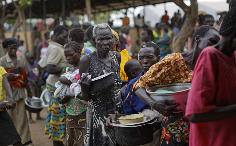 FILE – In this Tuesday, June 6, 2017 file photo, South Sudanese refugees queue to receive a lunch of maize mash and beans, at the Imvepi reception centre, where newly arrived refugees are processed before being allocated plots of land in nearby Bidi Bidi refugee settlement, in northern Uganda. The Trump administration on Wednesday, Sept. 6, 2017 imposed sanctions on two senior members of South Sudan's government, a former official, and three South Sudanese companies for undermining peace, security and stability in the crisis-stricken nation. (AP Photo/Ben Curtis, File)