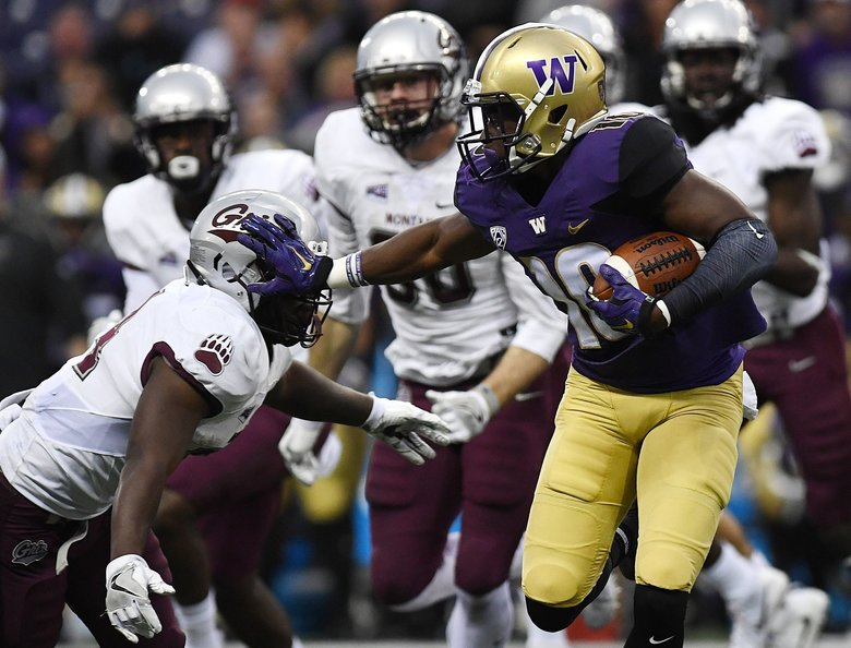 Jomon Dotson (10) stiff-arms Montana's Alijah Lee after Dotson intercepted a pass, sending Dotson on his way to a dynamic 68-yard TD return in a 63-7 UW win. (Tommy Martino/The Missoulian)