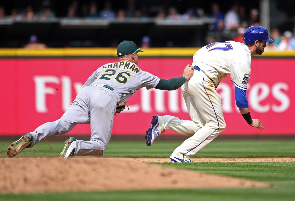 Mariners right fielder Mitch Haniger is tagged out on his way back to second base by Oakland third baseman Matt Chapman (26) during a fifth inning rundown.  (Ken Lambert/The Seattle Times)
