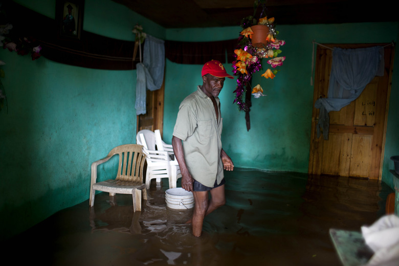 A man looks to salvage items from his flooded home after the passing of Hurricane Irma, in Fort-Liberte, Haiti, Friday Sept. 8, 2017. Irma rolled past the Dominican Republic and Haiti and battered the Turks and Caicos Islands early Friday with waves as high as 20 feet (6 meters). ( AP Photo/Dieu Nalio Chery)