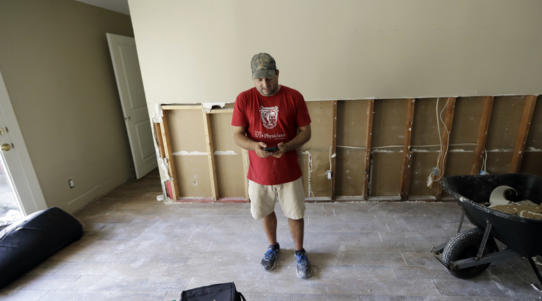 David Cummings checks his phone while cleaning up his home in the aftermath of Harvey Wednesday, Aug. 30, 2017, in Houston. Harvey did not discriminate in its destruction. It raged through neighborhoods rich and poor, black and white, upscale and working class. Across Houston and surrounding communities, no group sidestepped its paralyzing deluges and apocalyptic floods.  (AP Photo/David J. Phillip)