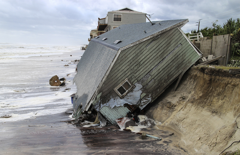 FILE – In this Monday, Sept. 11, 2017, file photo, a house slides into the Atlantic Ocean in the aftermath of Hurricane Irma at Ponte Vedra Beach, Fla. Florida and South Carolina, both hit by Irma, are among the dozen or so states that do not have dedicated disaster funds and opt to cover the expenses after the fact. (Gary Lloyd McCullough/The Florida Times-Union via AP, File)