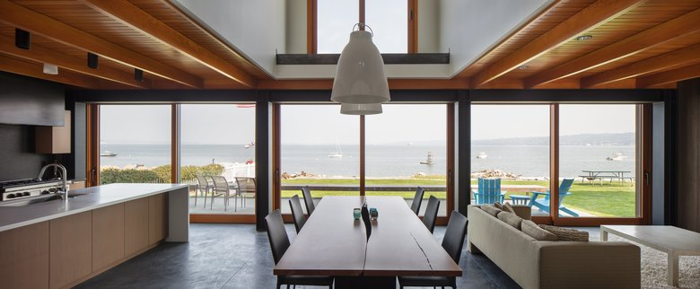 """A moment-frame, a huge piece of steel — that's how you have big glass doors,"" architect Erich Remash says of the great room. You also have a big view. ""Sitting here at night with the fire going, and the lights are dim, with the lights of Everett, sometimes ferries get close and cross each other,"" says homeowner Mike McMurray. (Steve Ringman/The Seattle Times)"