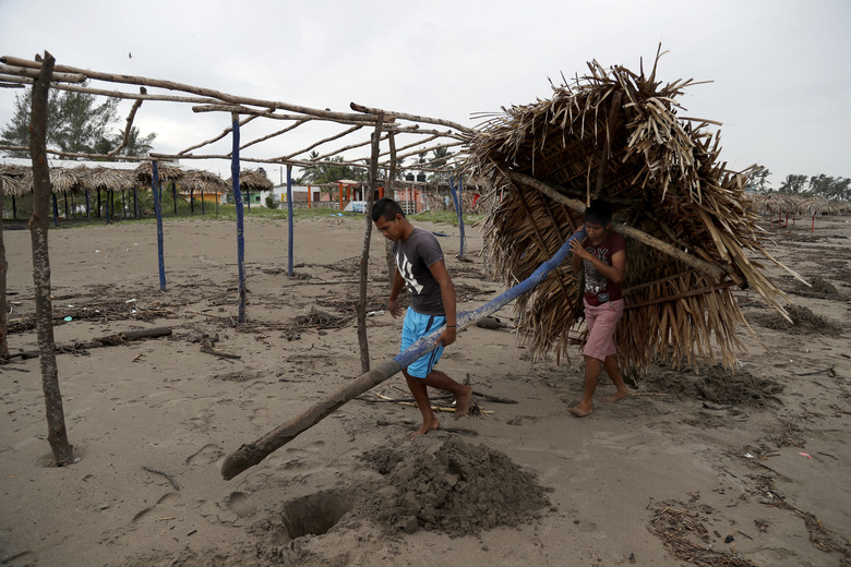 People moves a palm leave roof under an overcast sky before the arrival of Hurricane Katia, in Tecolutla, Veracruz state, Mexico, Friday, Sept. 8, 2017. Hurricane Katia in the Gulf of Mexico is stationary about 190 miles (310 kilometers) north-northeast of Veracruz and forecasters didn't expect much movement overnight. (AP Photo/Eduardo Verdugo)