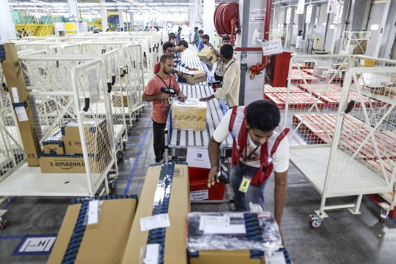 Employees work to prepare packages for shipment on the conveyor belt at the Amazon fulfillment center in Hyderabad.  (Dhiraj Singh/Bloomberg)