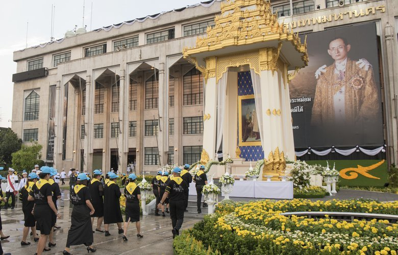 Thai volunteers stand in a line before laying down sandalwood flowers in front of a giant portrait of late Thai King Bhumibol Adulyadej in a replica of the royal crematorium in Bangkok, Thailand, Thursday, Oct. 26, 2017. The funeral of King Bhumibol Adulyadej, who reigned for 70 years before his death on Oct. 13, 2016. Bhumibol will be honored in an elaborate royal cremation ceremony from Oct. 25 to 29. (AP Photo/Kittinun Rodsupan) BKKR107 BKKR107
