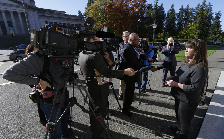 Stephanie McCleary, right, one of the plaintiffs in a lawsuit against the state of Washington regarding the funding of education, talks to reporters Oct. 24 after she attended arguments in a Washington Supreme Court hearing in Olympia.  (Ted S. Warren / The Associated Press)