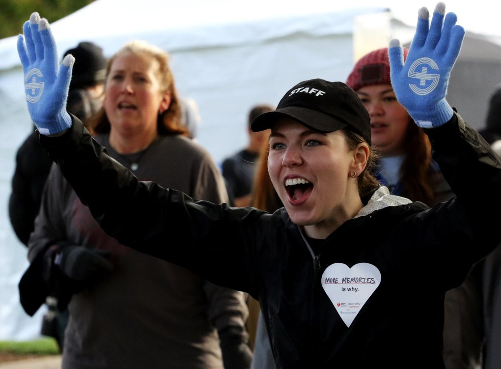 American Heart Association staffer Natalie Groce welcomes participants at the finish of the 5K fundraiser Saturday at Seattle Center.  (Alan Berner/The Seattle Times)