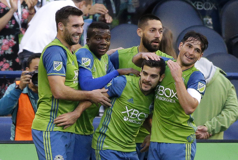 Sounders' midfielder Victor Rodriguez, second from lower right, is greeted by teammates after he scored a goal against FC Dallas in the first half last Sunday. (Ted S. Warren/AP)