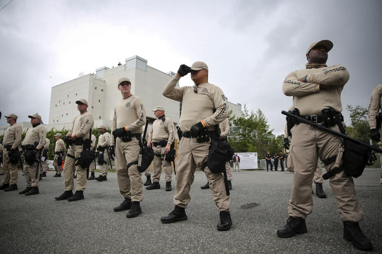 Troopers with the Florida Highway Patrol Quick Response Force line in front of the Phillips Center on the University of Florida campus in Gainesville ahead of white nationalist Richard Spencer's speech, Thursday, Oct. 19, 2017.  The school estimates it is spending $600,000 on security to ensure no repeat of violent clashes connected to a white nationalist gathering in Charlottesville, Va. (Will Vragovic/Tampa Bay Times via AP)