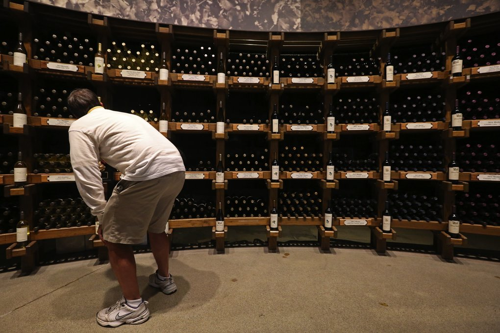 A visitor checks out wine for sale along a wall off Chateau Ste. Michelle's renovated and expanded tasting room. (Ken Lambert/The Seattle Times)