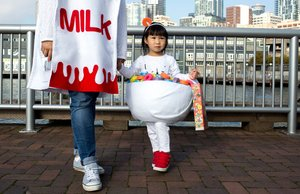 Dressed as a bowl of fruit loops Alyssa Chew (2.5) holds her mother's, Winnie Chew, hand as she is dressed as the matching milk carton during the Trick-or Treat on the Waterfront on Sunday, Oct. 29, 2017. Winnie Chew spent a week and a half making their costumes for this year. Approximately 20 businesses passed out candy to children dressed in costumes.