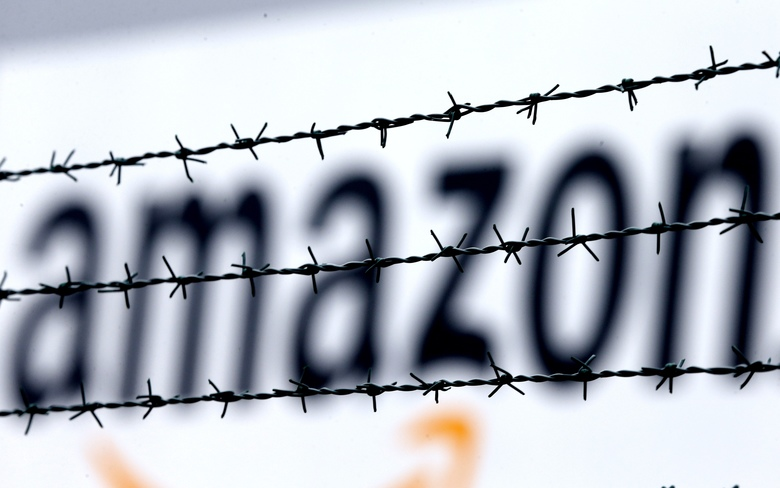 FILE – In this Feb. 19, 2013 file photo, the internet trader Amazon logo is seen behind barbed wire at the company's logistic center in Rheinberg,Germany. The European Union is telling member state Luxembourg to get $295 million in back taxes from Amazon in Brussels' latest regulatory move targeting U.S. tech companies accused of tax avoidance, it was reported on Wednesday, Oct. 4, 2017.  (AP Photo/Frank Augstein, File)