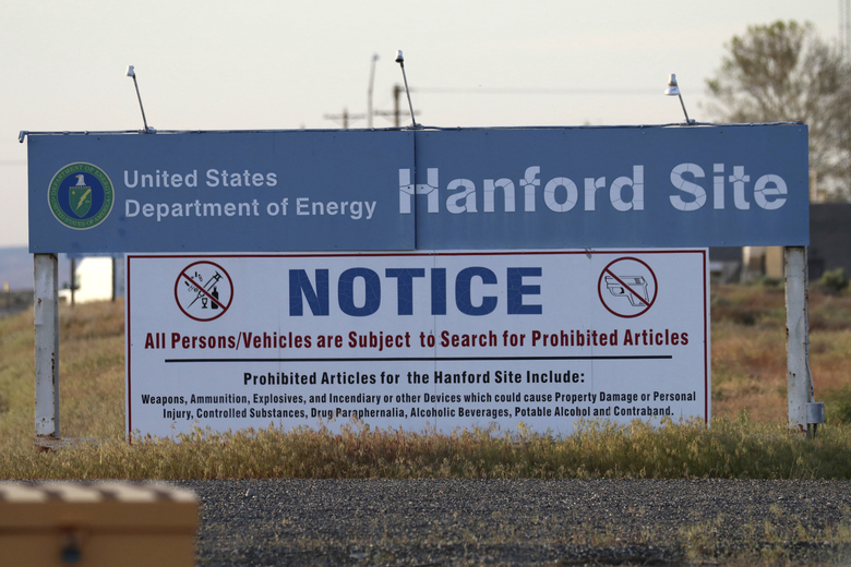 Signs are posted by the Hanford nuclear reservation in Richland. The U.S. Department of Energy said Wednesday that workers at Hanford have started injecting grout into a partially collapsed tunnel that contains radioactive wastes left over from the production of nuclear weapons.  (Manuel Valdes/AP)