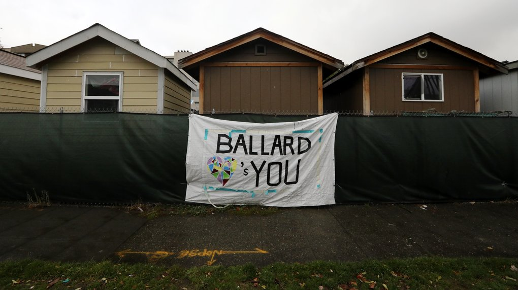 Nickelsville structures are seen above the fence facing the 2800 block of Market Street. With the camp's two-year permit expired, residents have prepared to move.  (Alan Berner/The Seattle Times)