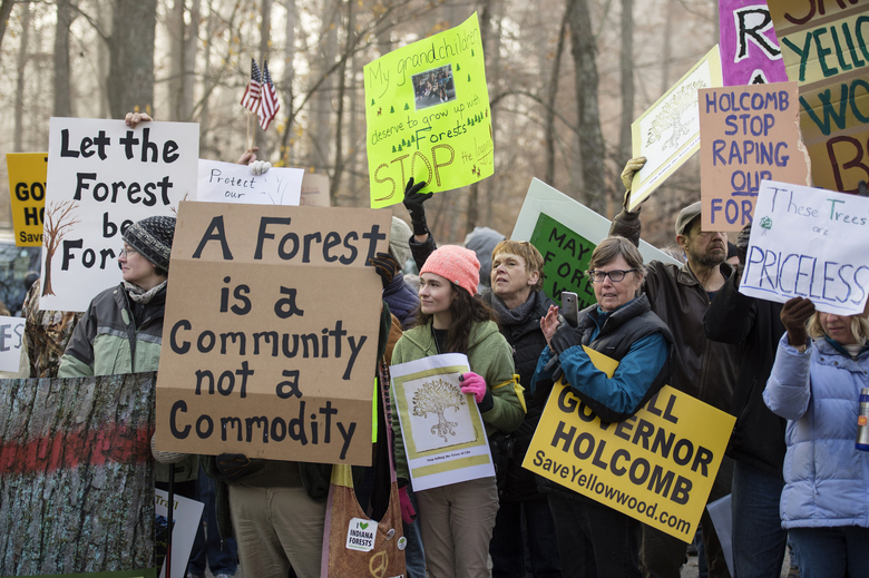"""Protestors gather at the Yellowwood State Forest office near Belmont, Ind. Thursday, Nov. 9, 2017 to protest the timber sale of more than 1,700 trees in old growth areas of the forest. Protestors yell """"Shame on you"""" as loggers make their way into the sale. (Chris Howell/The Herald-Times via AP)"""