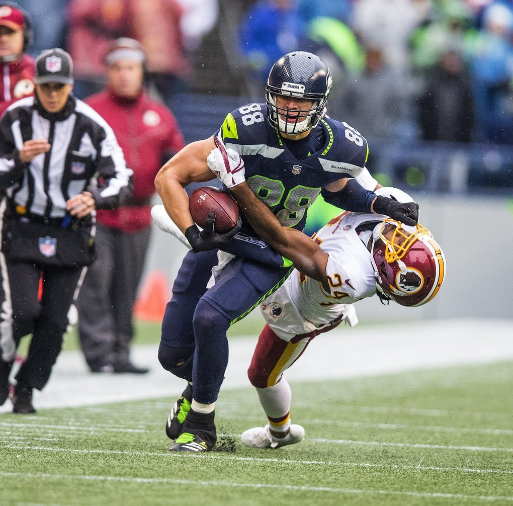 Seattle Seahawks tight end Jimmy Graham (88) gets pulled down by Washington cornerback Josh Norman (24). (Mike Siegel / The Seattle Times)