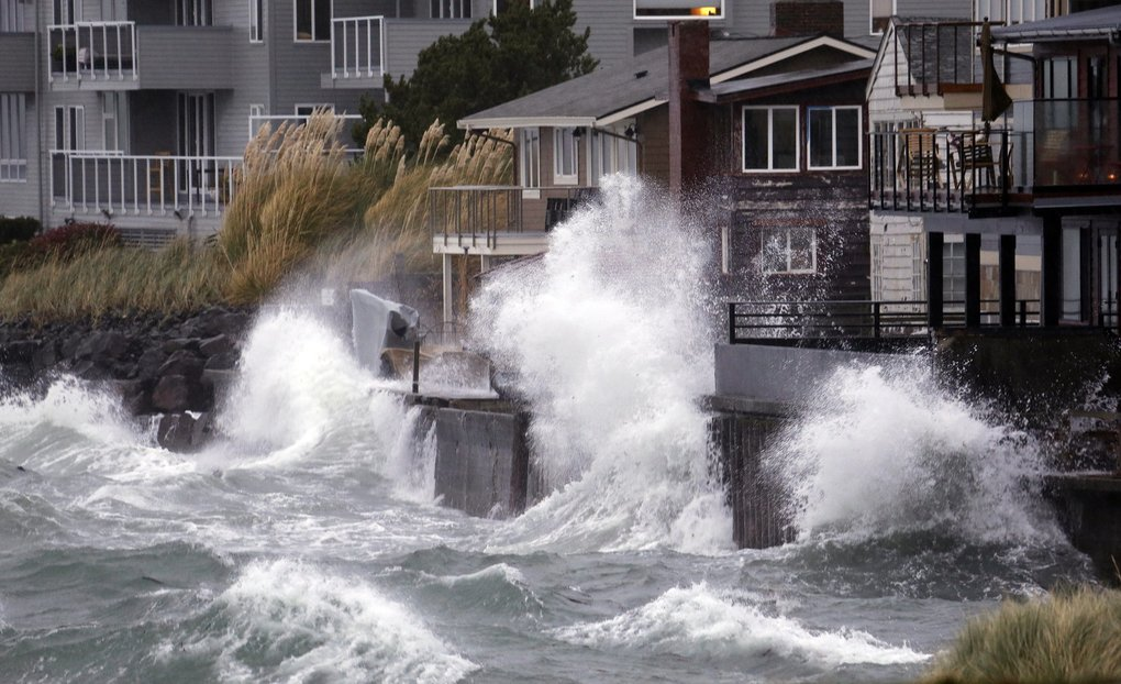 Waves striking a breakwater Monday send sheets of spray toward Seattle waterfront homes along Puget Sound. (Elaine Thompson / The Associated Press)