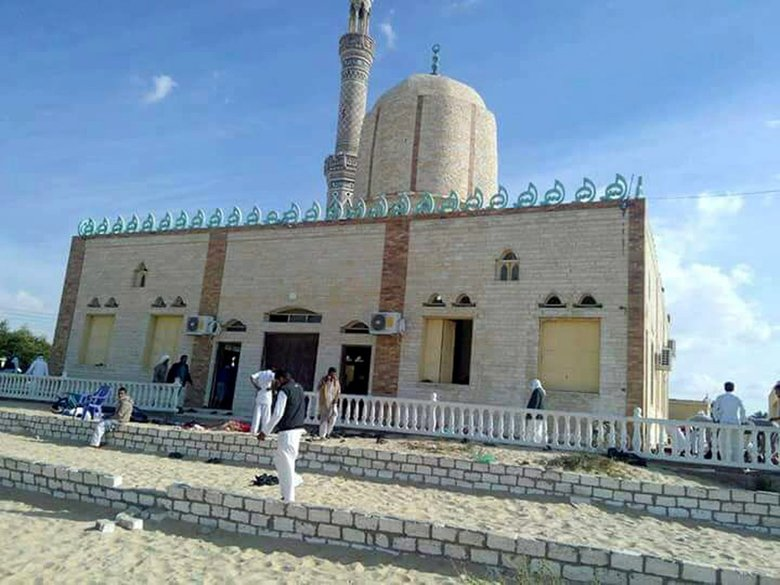 People walk outside a mosque that was attacked in the Sinai Peninsula in  Egypt on Friday. (European Pressphoto Agency)