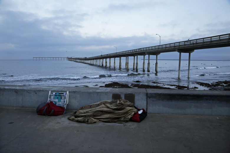 A person sleeps under a blanket on a beach near the Ocean Beach Pier in San Diego. A homeless crisis of unprecedented proportions is rocking the West Coast, leaving elected officials and outreach workers scrambling for solutions. (AP Photo/Gregory Bull)