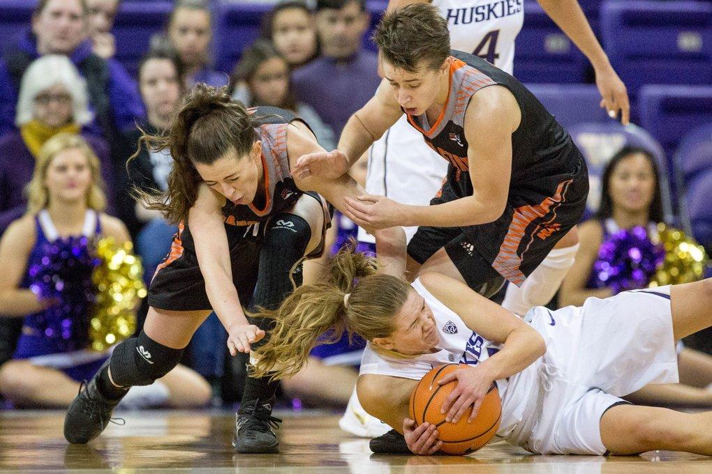 Washington Huskies guard Jenna Moser dives on the ground for the ball as Idaho State Bengals guard Grace Kenyon and Idaho State Bengals guard Dora Goles follow during a game at Alaska Airlines Arena in Seattle on Sunday. Idaho State Bengals won 79-59.   (Courtney Pedroza / The Seattle Times)