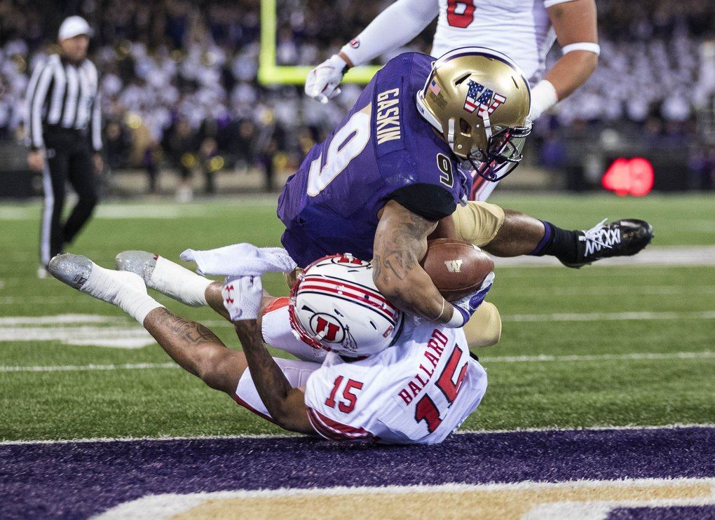 Myles Gaskin battles his way into the end zone for a 9-yard touchdown in the first quarter against Utah.   (Dean Rutz / The Seattle Times)