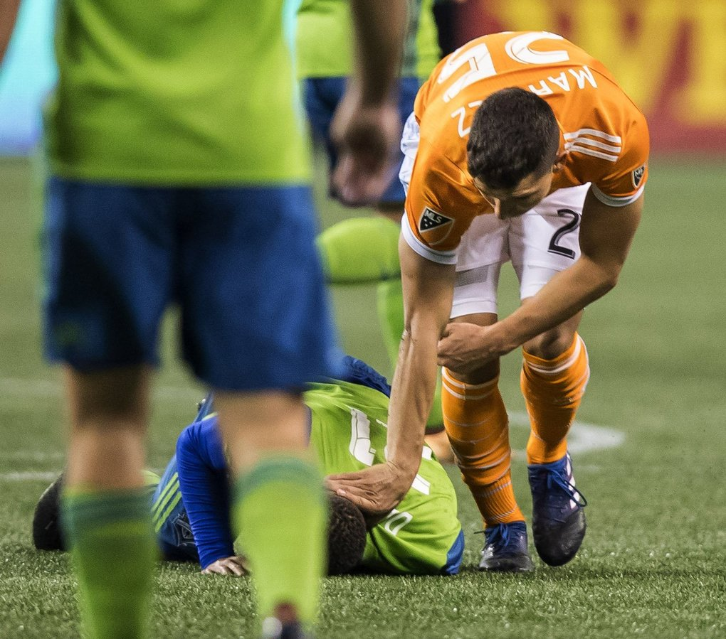 After colliding with Jordy Delem, Houston's Romas Martinez pushes Delem's face into the turf. Officials saw the incident on replay and issued a red card to Martinez. (Dean Rutz / The Seattle Times)