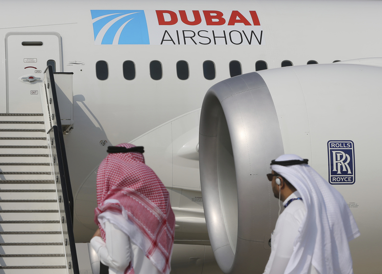 Emirati visitors walk past a Boeing 787-10 Dreamliner during the opening day of the Dubai Air Show on Sunday. The show opened with Emirates making a $15.1 billion deal to buy Boeing 787-10 Dreamliners. (Kamran Jebreili/AP)