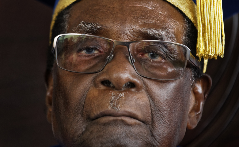 FILE – In this Friday Nov. 17, 2017 file photo, Zimbabwean President Robert Mugabe attends a graduation ceremony on the outskirts of Harare. Zimbabwe's Parliament erupted in cheers Tuesday Nov. 21, 2017 after the speaker announced the resignation of President Robert Mugabe after 37 years in power. (AP Photo/Ben Curtis, File)