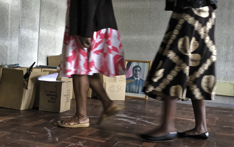 Workers walk past a photograph of President Robert Mugabe at a government building in Harare, Zimbabwe Thursday, Nov. 16, 2017. Zimbabweans faced another day of uncertainty amid quiet talks to resolve the country's political turmoil and the likely end of President Robert Mugabe's decades-long rule. (AP Photo/Ben Curtis)