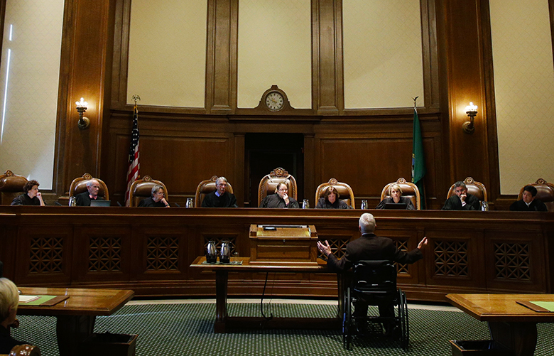 Tom Ahearne, center-right, the lead attorney in a lawsuit against the state of Washington regarding the funding of education, gestures as he speaks Tuesday, Oct. 24, 2017, during a Washington Supreme Court hearing in Olympia, Wash. The hearing was held to determine if Washington state has complied with a court mandate to fully fund the state's basic education system. (AP Photo/Ted S. Warren)