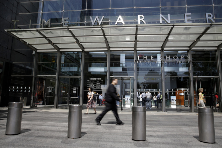 "FILE – In this Tuesday, May 26, 2015, file photo, pedestrians walk by an entrance to the Time Warner Center in New York. AT&T now says it's ""uncertain"" when its $85 billion Time Warner purchase will close. AT&T had maintained that the deal would be done by the end of 2017. (AP Photo/Mary Altaffer, File)"