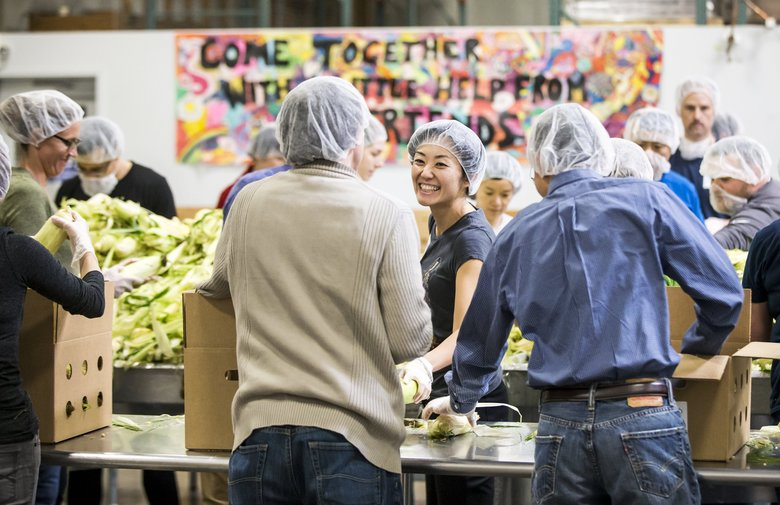 Ying Hao is among volunteers from Microsoft packing corn for local food banks in October at Northwest Harvest in Kent. (Bettina Hansen / The Seattle Times)