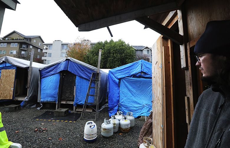 "Chris Teel, a resident of Ballard's ""Nickelsville,"" is prepared to move as its two-year permit expires. Modern apartments rise above the shelters behind it in the 2800 block of Market St.   Seattle says they've extended it because the new site for the city-sanctioned tent camp (one of 6 citywide) in Wallingford is not ready.
