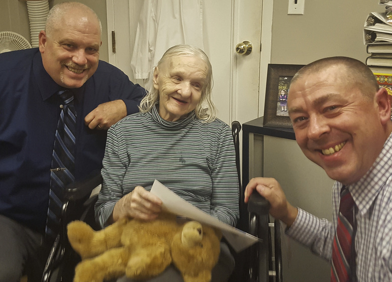 FILE – This October 2017 file photo provided by the Sullivan County Sheriff's Office shows Flora Harris, center, with Sullivan County Sheriff's Detective Sgt. Ed Clouse, left, and Detective Rich Morgan at an assisted living residence in Lowell, Mass. Harris, who disappeared from upstate New York in 1975, has been found suffering from dementia and living in the assisted-living facility in Massachusetts, authorities said. Officials said they've been unable to figure out details of what happened to her between the time she disappeared and when she was finally found. (Sullivan County Sheriff's Office via AP, File)