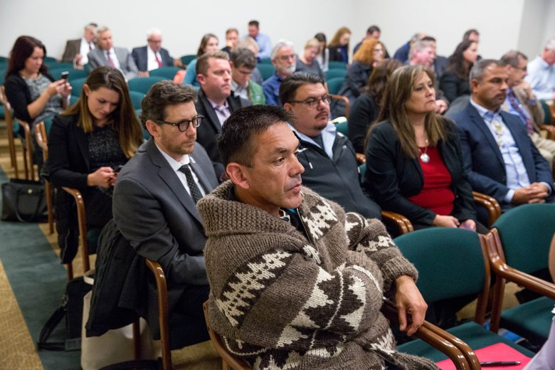 Jeremiah Julius, chairman of the Lummi Nation, front, listens to Innes Weir, Cooke Aquaculture Pacific manager, speak at a hearing with the House Agriculture and Natural Resources Committee about the Cooke fish escape.  (Courtney Pedroza/The Seattle Times)