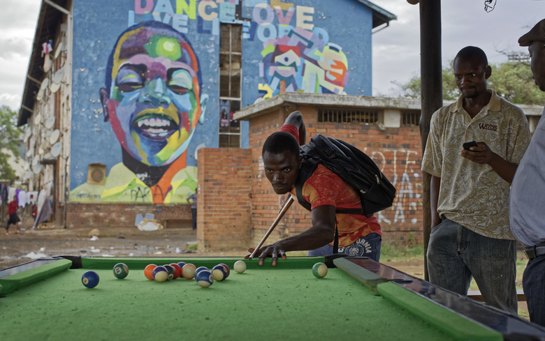 Men play pool at an open-air pool hall next to an apartment block  in the low-income neighborhood of Mbare in Harare, Zimbabwe Thursday, Nov. 16, 2017. Zimbabweans faced another day of uncertainty amid quiet talks to resolve the country's turmoil and the likely end of President Robert Mugabe's decades-long rule. (AP Photo/Ben Curtis)