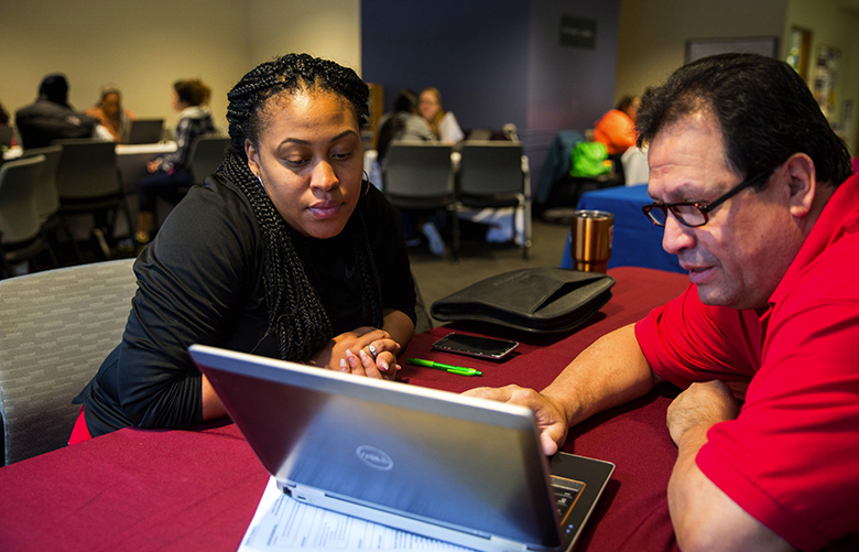Nikita Milord works with Enrique Palacios a client services specialist navigator with Public Health – Seattle & King County to find a healthcare option for her and her daughter during an event to register people the ACA at the Columbia Public Health Center in Columbia City on Saturday, Nov. 4,  2017.   204062