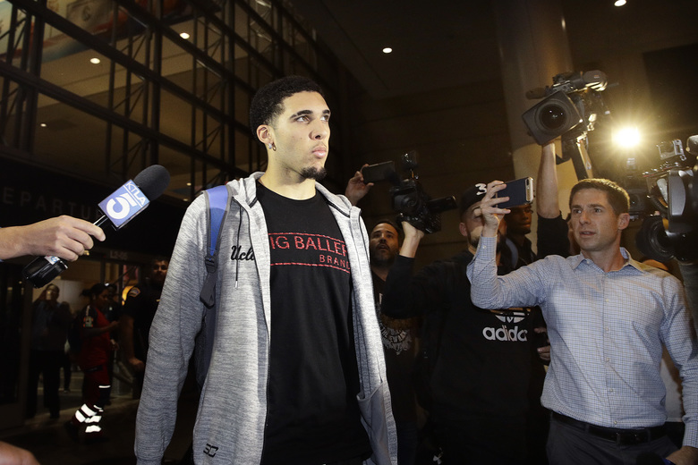 UCLA basketball player LiAngelo Ball is surrounded by reporters and photographers as he leaves Los Angeles International Airport on Tuesday. Three UCLA basketball players detained in China on suspicion of shoplifting returned home, where they may be disciplined by the school. (AP Photo/Jae C. Hong)