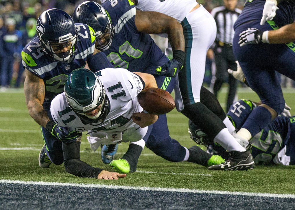 Philadelphia Eagles quarterback Carson Wentz (11) fumbles the ball near the goal line and into the end zone as Seattle Seahawks' Earl Thomas (29) and Sheldon Richardson (91) move in during the second half.  (Mike Siegel / The Seattle Times)