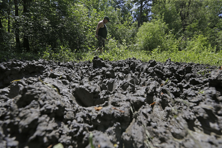 FILE – In this June 17, 2014, file photo, a wildlife trapper, walks past damage from feral hogs that happened overnight while foraging near one of his traps in New Orleans. Tests of poison bait for feral hogs are planned in Texas and Alabama, and that's a big step toward possible control of beasts which do well over $1.5 billion a year in damage around the country: If all goes well, the bait could get federal approval in 2020. (AP Photo/Gerald Herbert, File)