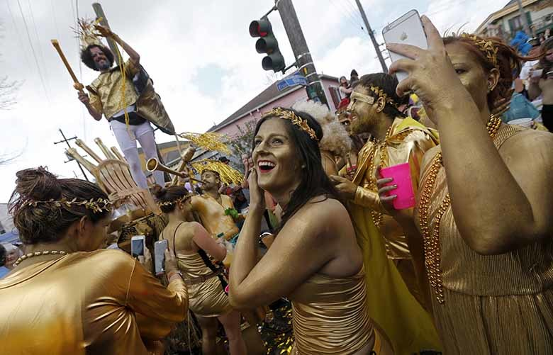 FILE – In this Feb. 28, 2017, file photo, revelers congregate at the start of the Society of Saint Anne Mardi Gras parade in New Orleans. The city celebrates its tricentennial in 2018. (AP Photo/Gerald Herbert, File)
