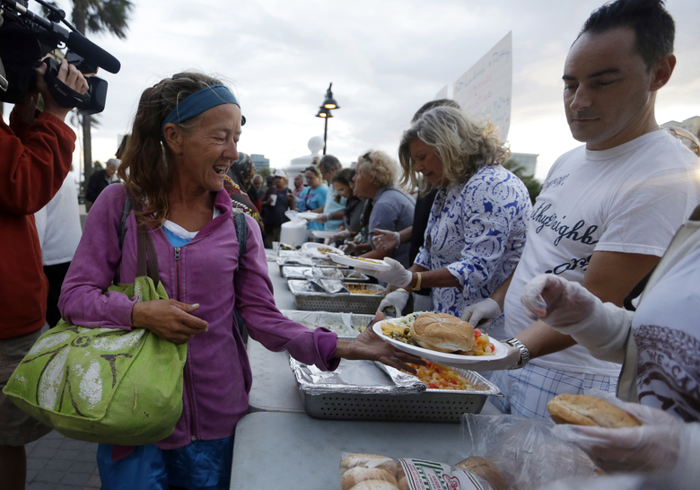 FILE – In this Nov. 5, 2014, file photo, members of the homeless community are served meals by advocates in Fort Lauderdale, Fla. Volunteers who feed the homeless in public places say they're providing a needed service. But city governments and some advocates say their well-meaning efforts can hinder long-term solutions and raise sanitation concerns. (AP Photo/Lynne Sladky, File)
