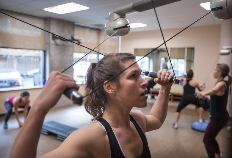 Erin Carstens works out with cables on a kinesis machine at 5focus Movement Studio in Seattle. The workouts focus on core stability and balance. (Steve Ringman/The Seattle Times)